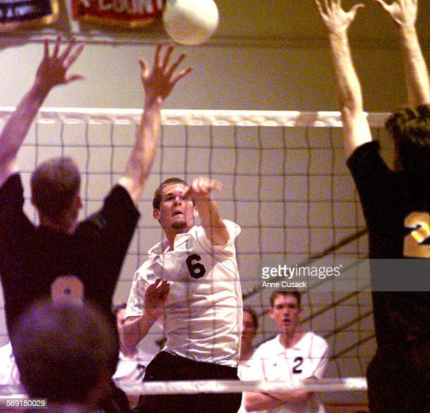 Thousand Oaks Shane Maguire outside hitter hits the ball as Ryan Denihan and Nick Flanagan both of Roayal HS try to block during second game at TO HS