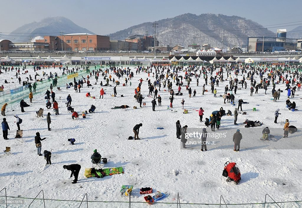 Thousands of anglers cast lines through holes created in the surface of a frozen river during an ice fishing contest in Hwacheon, 120 kilometers northeast of Seoul, on January 6, 2013. The contest is part of an annual ice festival which draws over 1,000,000 visitors every year. AFP PHOTO / JUNG YEON-JE