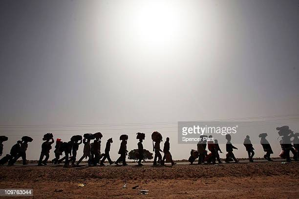 Thousands of Bangladeshi migrant workers who recently crossed into Tunisia from Libya walk to a United Nations displacement camp March 04 2011 in Ras...
