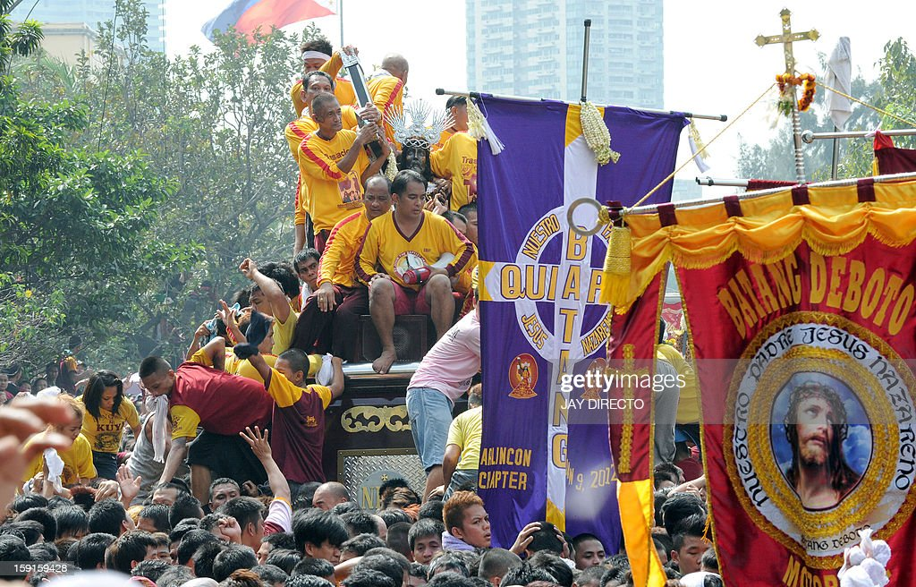Thousands of Catholic devotees jostle for positions as they climb over one another to try to kiss the cross (C) draped on the statue of Black Nazarene during the annual procession in honor of the centuries-old icon of Jesus Christ in Manila on January 9, 2013. Masses of Catholic devotees swept through the Philippine capital on January 9 in a spectacular outpouring of passion for a centuries-old icon of Jesus Christ that many believe can perform miracles. AFP PHOTO / Jay DIRECTO