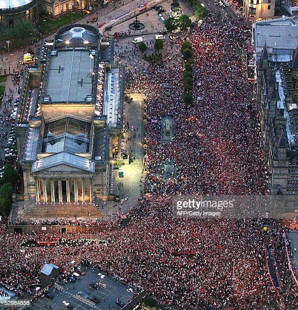 Thousands of fans cheer the Liverpool football team during a parade to welcome them home 26 May following their Champions League victory over AC...