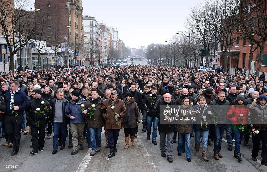 Thousands of French policemen take part in a silent march on February 26, 2013 in Paris, in the memory of two of their colleagues, killed in a collision five days before in Paris during a high-speed chase. An alleged drunk driver killed the two Paris police officers after slamming his black Land Rover into their cruiser during a high-speed chase on the ring road around Paris. AFP PHOTO / ERIC FEFERBERG