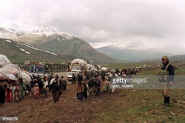 Thousands of Iraqi Kurdish refugees cross the IraqIran border at Hadji Omran point near Piranshar 12 April 1991 while an Iranian soldier looks on...