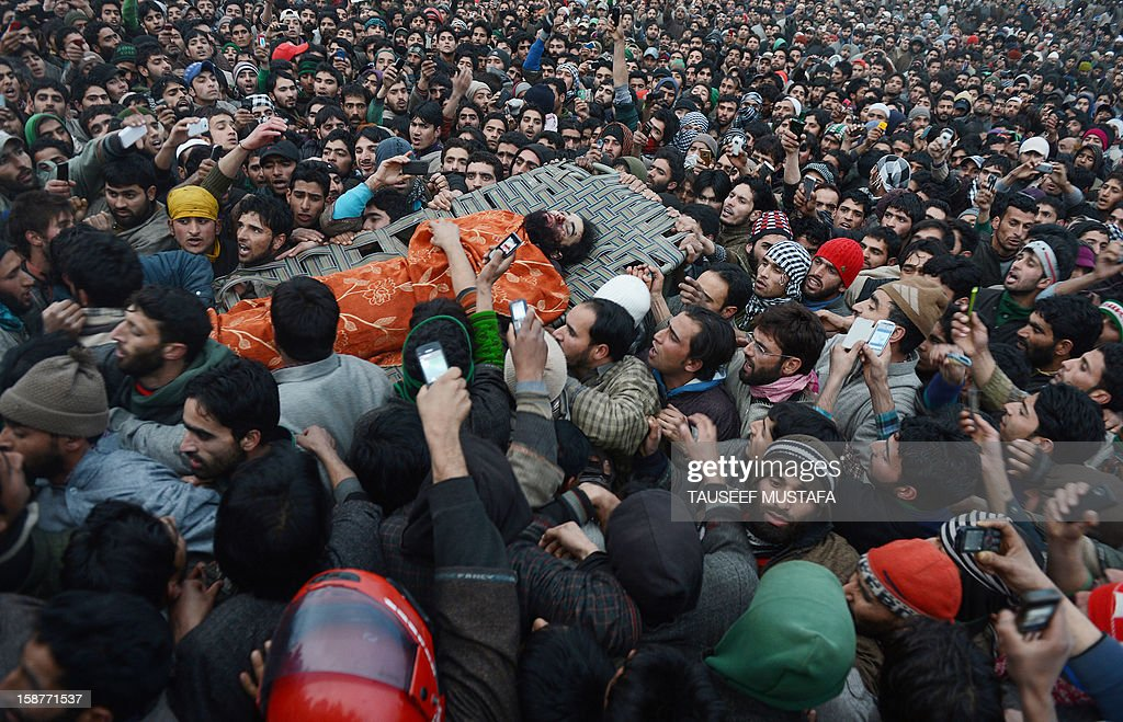 Thousands of Kashmiri Muslims carry a body of Lashkar-e-Toiba militant, Imtiyaz Ahmed, during a funeral at Pulwama some 55kms south of Srinagar on December 28,2012. Indian troops shot dead two suspected Islamic militants in Kashmir while seven civilians received police bullet injuries when they protested the slaying of the rebels, officials said. The two militants belonging to the Pakistan-based Lashkar-e-Taiba rebel group were killed while three troopers were wounded in a firefight with militants in Pulwama.AFP PHOTO/ Tauseef MUSTAFA