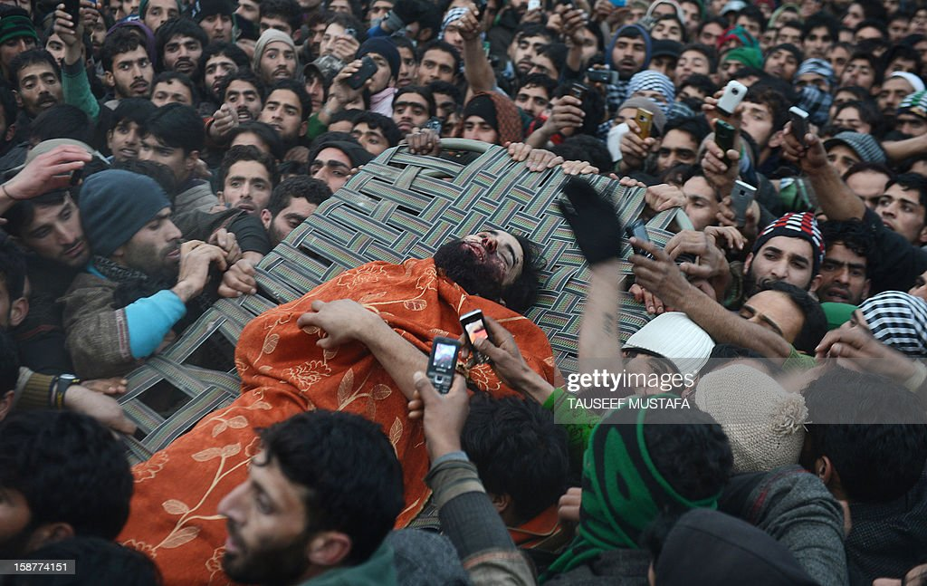 Thousands of Kashmiri Muslims carry a body of Lashkar-e-Toiba militant, Imtiyaz Ahmed, during a funeral at Pulwama some 55kms south of Srinagar on December 28,2012. Indian troops shot dead two suspected Islamic militants in Kashmir while seven civilians received police bullet injuries when they protested the slaying of the rebels, officials said. The two militants belonging to the Pakistan-based Lashkar-e-Taiba rebel group were killed while three troopers were wounded in a firefight with militants in Pulwama town.AFP PHOTO/ Tauseef MUSTAFA