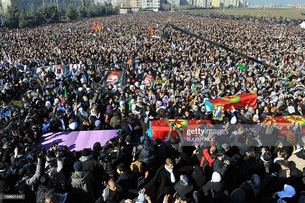 Thousands of Kurds carry the coffins of the three top Kurdish activists Sakine Cansiz, Fidan Dogan and Leyla Soylemez, shot dead in the French capital, on January 17 in Diyarbakir. Several thousand Kurds gathered Thursday in a square in Diyarbakir, the main city of Turkey's Kurd-majority southeast, to pay a final tribute to three Kurdish women activists who were assassinated in Paris last week. The growing crowd of participants, men and women adorned in white scarves, a symbol of peace, marched in a funeral many in Turkey feared would turn into a violent protest. The three women, one of them Sakine Cansiz, a co-founder of the outlawed Kurdistan Workers' Party (PKK), were found fatally shot, at least three times in their heads, at a Kurdish centre in Paris last week. French police were hunting the unknown assailants. AFP PHOTO/BULENT KILIC