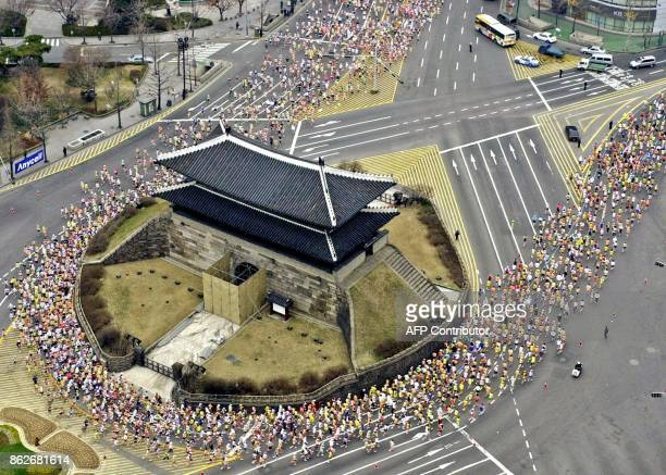 Thousands of marathon runners make their turn at the Namdaemun a historic gate in central Seoul 16 March 2003 during the DongA Seoul International...