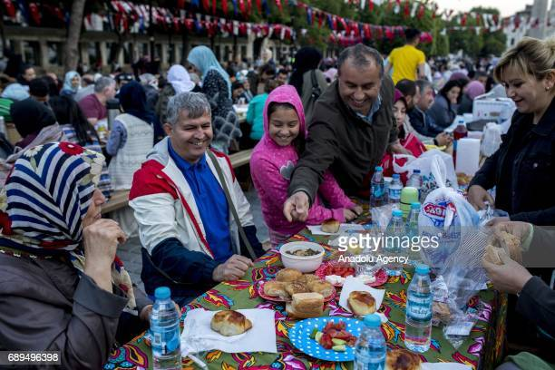 Thousands of Muslims gather to break their fast at a fastbreaking dinner on the Muslims' holiest month of Ramadan at Sultanahmet Square where hosts...
