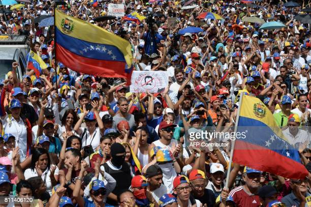 Thousands of opposition activists take part in a demonstration marking 100 days of protests against Venezuelan President Nicolas Maduro in Caracas on...