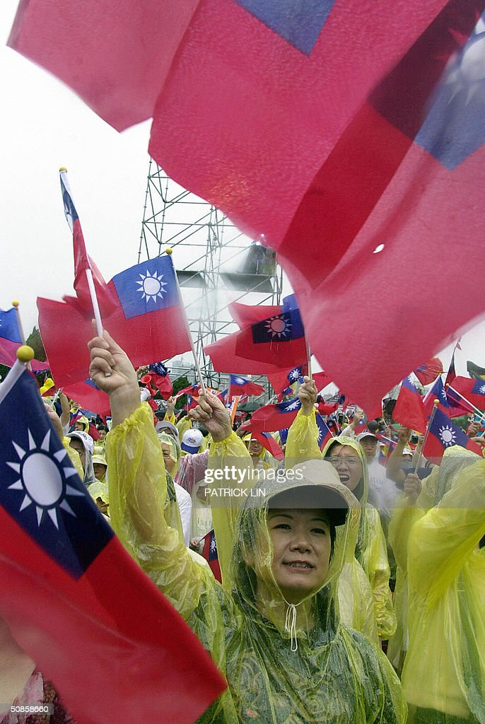 Thousands of opposition supporters clad in raincoats, wave Taiwanese national flags during a protest rally in Taipei, 20 May 2004 as President Chen is sworn in for a second four-year term. The opposition is disputing Chen's re-election claiming it was the result of unfair election. Chen won the 20 March presidential polls by a razor-thin margin of 0.22 percent, or 30,000 votes.