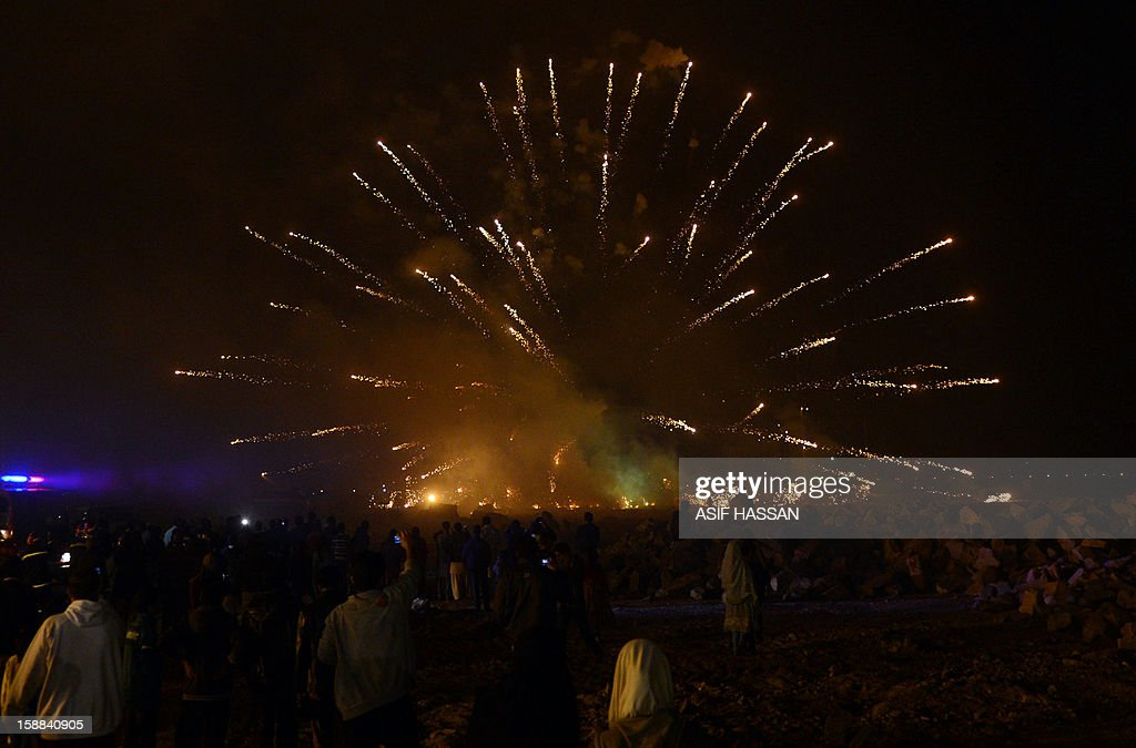 Thousands of Pakistanis watch fireworks at Clifton beach in Karachi to celebrate the New Year early on January 1, 2013. World cities from Sydney and Hong Kong to Dubai and London rang in the New Year with spectacular fireworks, as revelers at Times Square in New York sought to top off the global extravaganza. AFP PHOTO / Asif HASSAN
