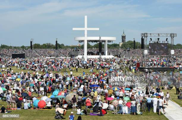 Thousand's of participants follow the final mass of the Kirchentag festival celebrating the 500th anniversary of the Reformation at a meadow near the...