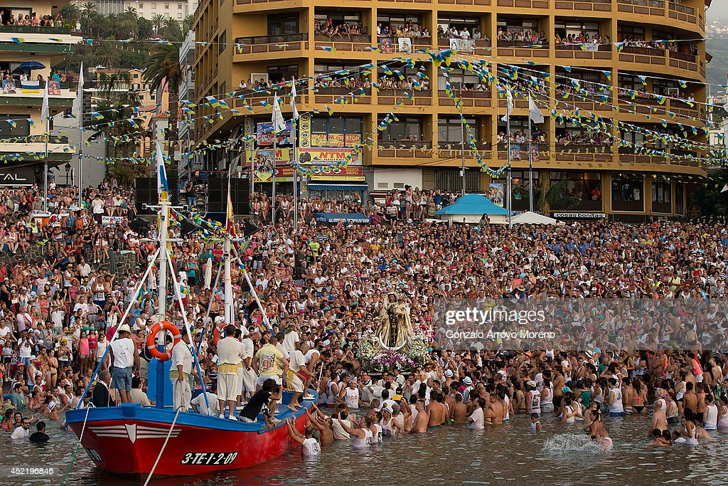 Thousands of people attends carriers of the Great God Power brotherhood holding the Virgen del Carmen statue prior to be loaded on July 15, 2014 at Puerto de la Cruz dock on the Canary island of Tenerife, Spain. Since 1921, the statue of the Virgen del Carmen, patron saint of fishermen, has been carried with great fanfare annually as part of July Festivities to the Puerto de la Cruz dock where, at the end of its procession, it is hoisted aboard a decorated boat. Weather permitting, the boat carrying the statue, accompanied by a flotilla of other boats, makes a short journey along the island coast before returning to the harbour. In recent years, attendance at the event has numbered more than 35,000 people.