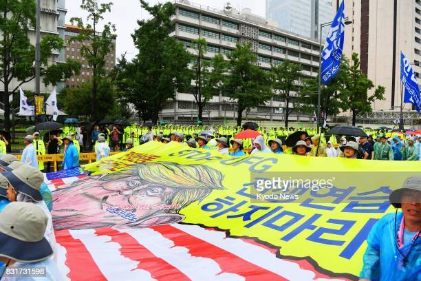 Thousands of people belonging to leftleaning civic groups and labor unions hold a banner depicting US President Donald Trump in front of the US...