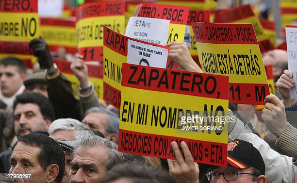 Thousands of people holding placards reading 'Zapatero in my name no negotiations with murderers ETA' stage a protest a day after a bomb exploded in...