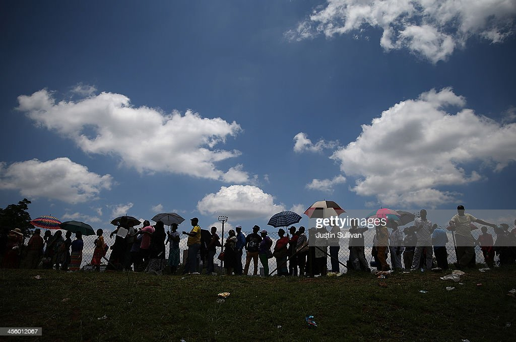 Thousands of people line up to board a bus that will take them to wait in line to view the body of former South African president Nelson Mandela as he lies in state at the Union Buildings on December 13, 2013 in Pretoria, South Africa. Nelson Mandela's body will lie in state for three days as part of a week of events commemorating the life of former South African President. Mr Mandela passed away on the evening of December 5, 2013 at his home in Houghton at the age of 95. Mandela became South Africa's first black president in 1994 after spending 27 years in jail for his activism against apartheid in a racially-divided South Africa.
