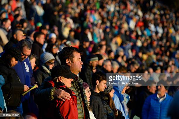 Thousands of people listen to the morning prayer as the sun begins to rise during the 68th annual Easter sunrise service at Red Rocks Amphitheatre in...