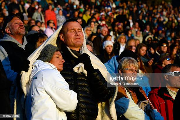 Thousands of people listen to the saying of the Lord's Paryer as the sun begins to rise during the 68th annual Easter sunrise service at Red Rocks...