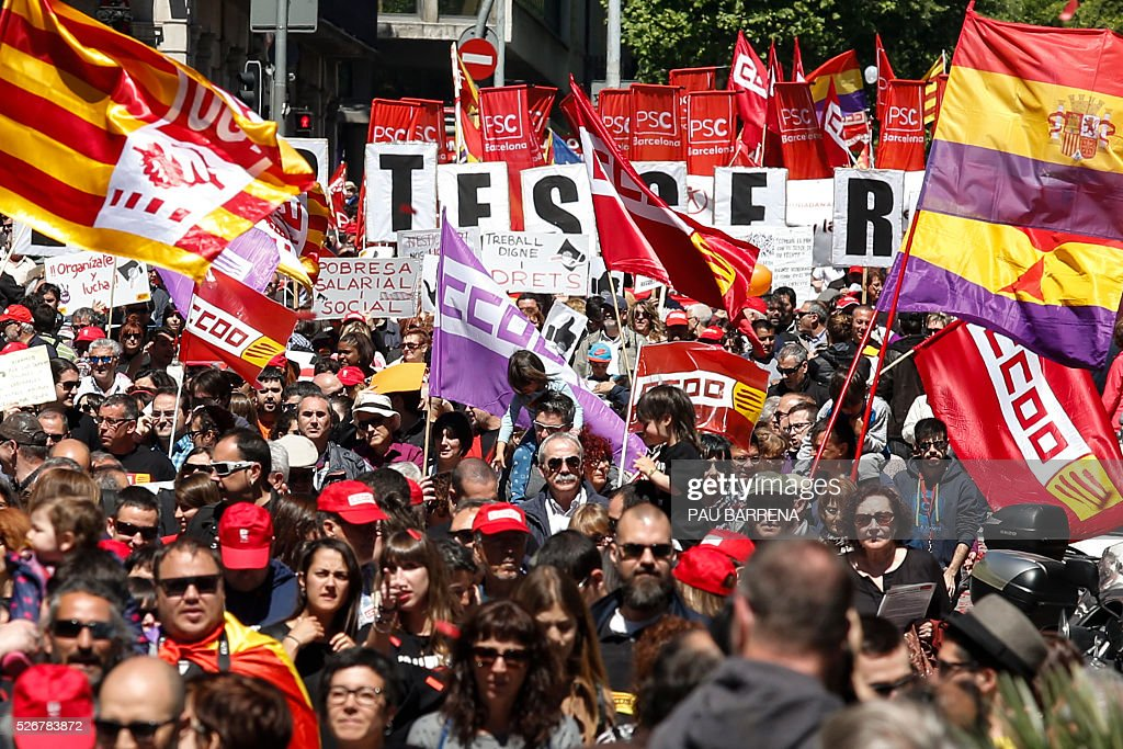 Thousands of people march with flags and placards during the traditional May Day rally called by Spanish unions in Barcelona on May 1, 2016. / AFP / PAU