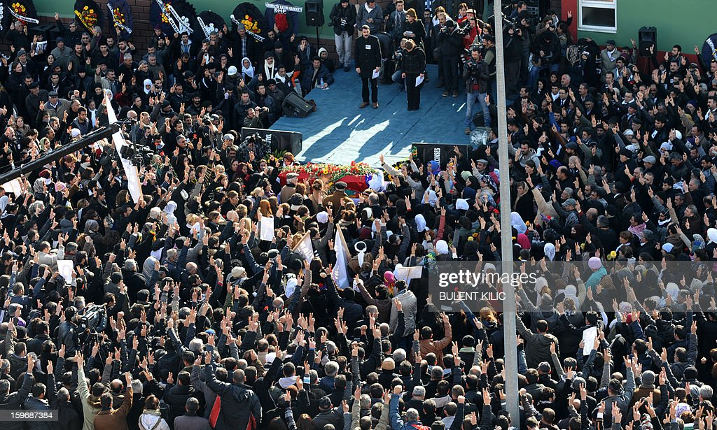 Thousands of people pay their respects around the coffin of late Kurdish activist Sakine Cansiz, shot dead in the French capital, during the funeral on January 18, 2013 in Tunceli, her hometown in the Kurdish majority southeast of Turkey. People gathered inTunceli, to pay a final tribute to Sakine Cansiz who was assassinated in Paris last week. The growing crowd of participants, men and women adorned in white scarves, a symbol of peace, marched in a funeral many in Turkey feared would turn into a violent protest. The three women, one of them Sakine Cansiz, a co-founder of the outlawed Kurdistan Workers' Party (PKK), were found fatally shot, at least three times in their heads, at a Kurdish centre in Paris last week. French police were hunting the unknown assailants. AFP PHOTO/BULENT KILIC