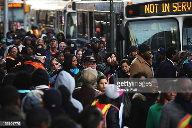 Thousands of people wait to board city buses into Manhattan at the newly opened Barclay's Center as the city continues to recover from superstorm...
