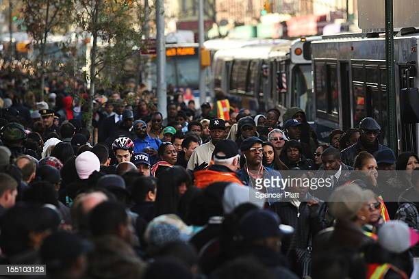 Thousands of people wait to board city buses into Manhattan at the newly opened Barclay's Center in Brooklyn as the city continues to recover from...