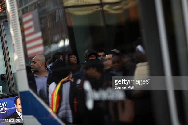 Thousands of people wait to board city buses into Manhattan in Brooklyn as the city continues to recover from superstorm Sandy on November 1 in New...