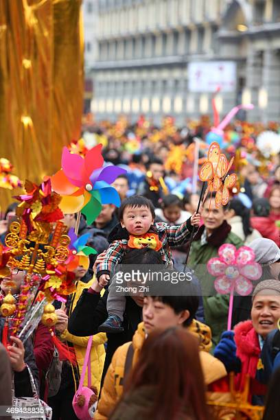 Thousands of people walk across the Tongji Bridge with pinwheels and throw lettuce into a fountain to pray for good blessing during the Lantern...