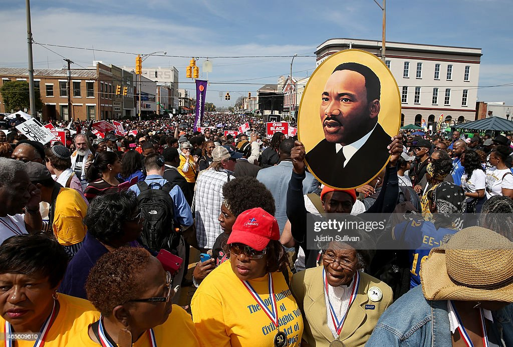 Thousands of people walk down Broad Street towards the Edmund Pettus Bridge during the 50th anniversary commemoration of the Selma to Montgomery...