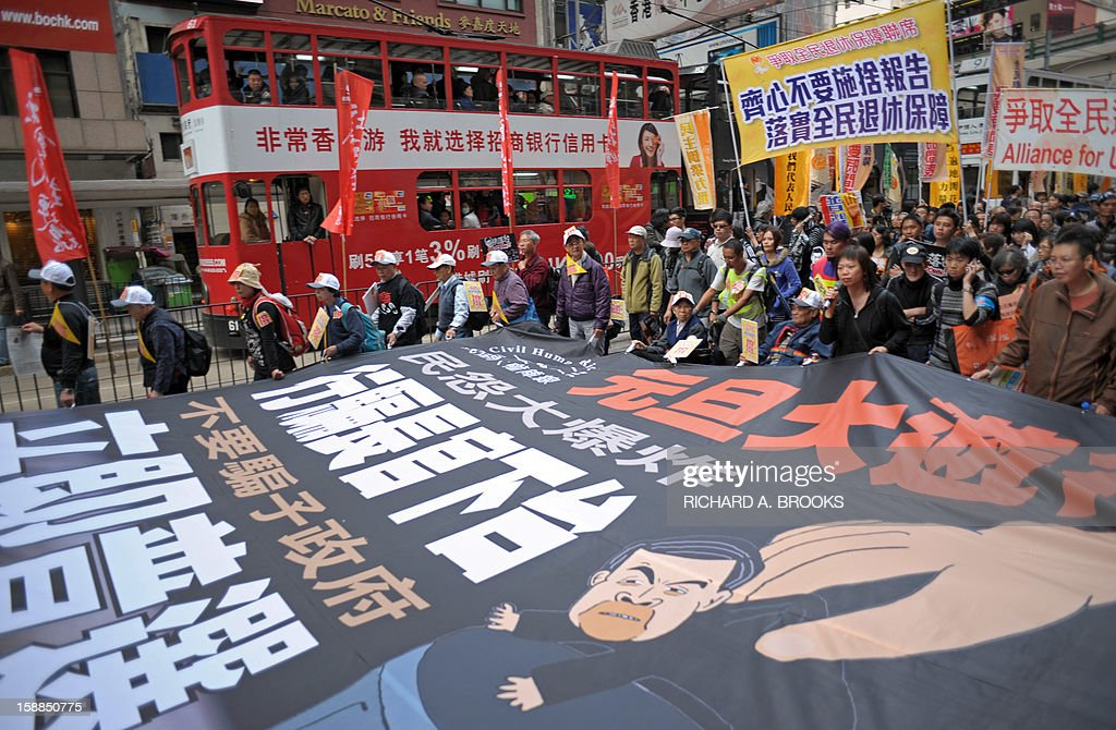 Thousands of pro-democracy protesters take to the streets calling for new Hong Kong Chief Executive Leung Chun-ying to step down in Hong Kong on January 1, 2013. Organisers have said they expected 50,000 people to join the New Year's Day march against Leung Chun-ying, while pro-government groups staged separate and smaller rallies in support of the Beijing-backed chief executive. AFP PHOTO / RICHARD A. BROOKS