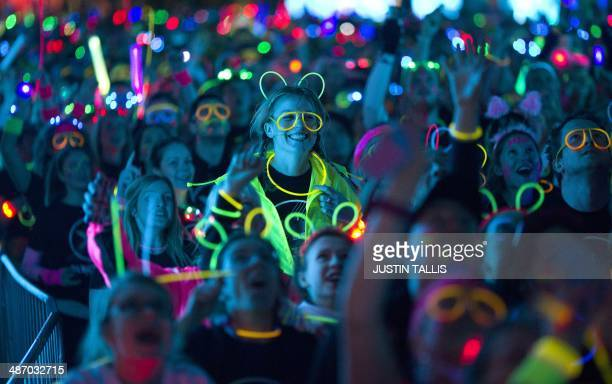 Thousands of revelers wearing neoncoloured clothes take part in the 5km Electric Run around Wembley Stadium in London on April 26 2014 AFP PHOTO /...