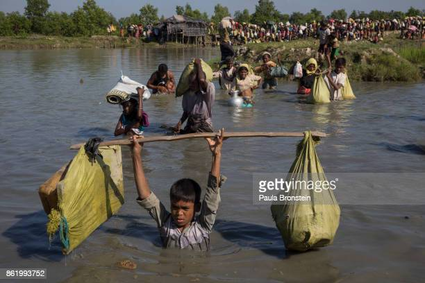 Thousands of Rohingya refugees fleeing from Myanmar cross a small stream in the hot sun on a muddy rice field on October 16 2017 near Palang Khali...