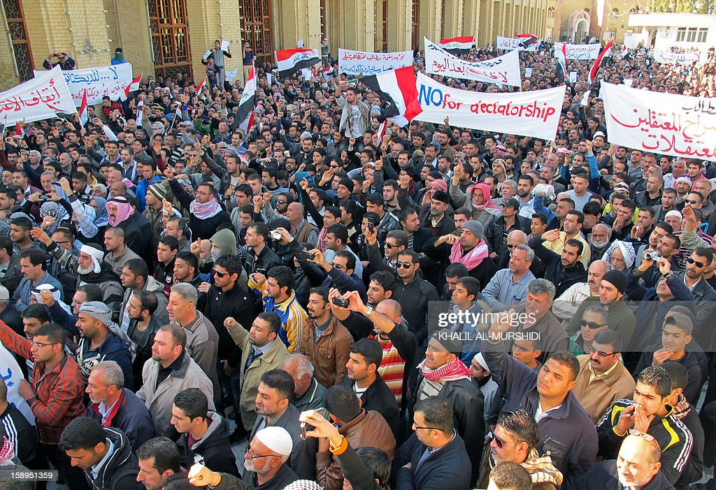 Thousands of Sunni Muslim protestors hold banners and wave their national flag during a demonstration on January 4, 2013 criticising Iraq's premier and demanding the release of prisoners they say are wronglfully held, near Abu Hanifa mosque, in the mostly Sunni Muslim neighbourhood of Aldhamiya in Baghdad. The protesters held up banners calling for a mass prisoner release, stronger human rights provisions in Iraq's prisons, and a repeal of current anti-terror legislation.