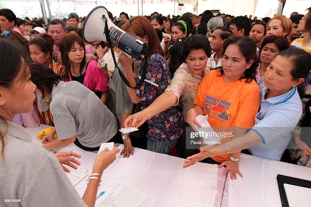 Thousands of Thais wait for hours to receive a government check of 2000-baht ($57.00 US) at the City hall March 26, 2009 in Bangkok, Thailand. The pay out is being given to stimulate an economy battered by the global financial crisis. Eight million Thais have been unemployed since September 1, 2008, and in total there are 9.4 million people who make less than 15000 baht per month and are eligible for the cash hand-out. Today 20,000 red-shirted protesters surrounded the prime minister's office demanding the government resign. The pro-Thaksin supporters claim that Prime Minister Abhisit Vejjajiva government came to power through illegal means and are demanding elections.