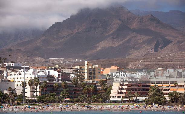 Thousands of tourists sunbathe on the beach of Las Vistas in Los Cristianos on the southern coast of the Canary island of Tenerife on July 25 2015...
