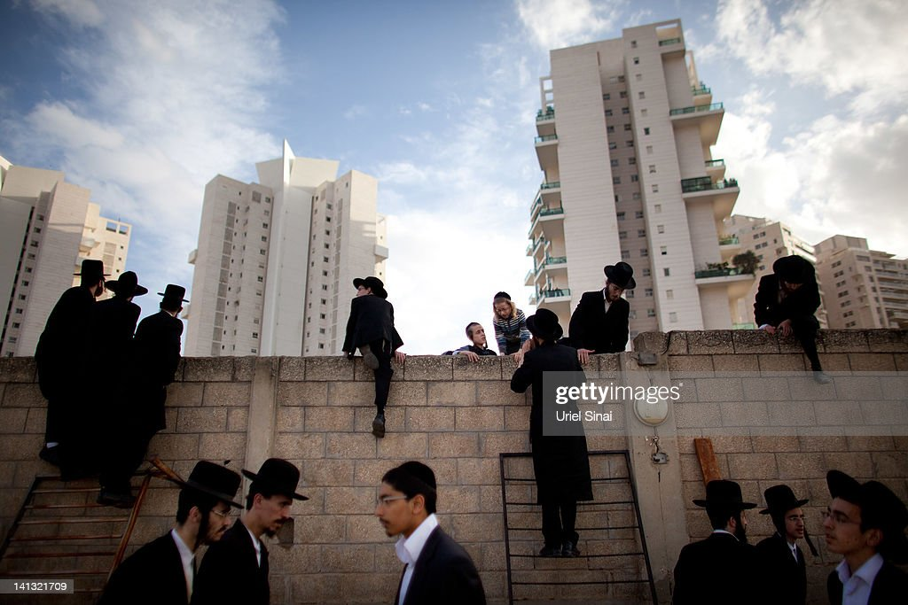 Thousands of ultra-Orthodox Jews of the Vizhnitz Hasidic dynasty stand on ladders as they follow the funeral procession of their rabbi Moshe Yhoshua Hager's body wrapped in a prayer Shawl before his funeral on March 14, 2012 in Bnei Brak, Israel. Rabbi Moshe Yehoshua Hager, who was the head of Israel's second largest Hasidic community, died aged 95 and was buried beside his father's grave in the Tel Aviv suburb of Brei .