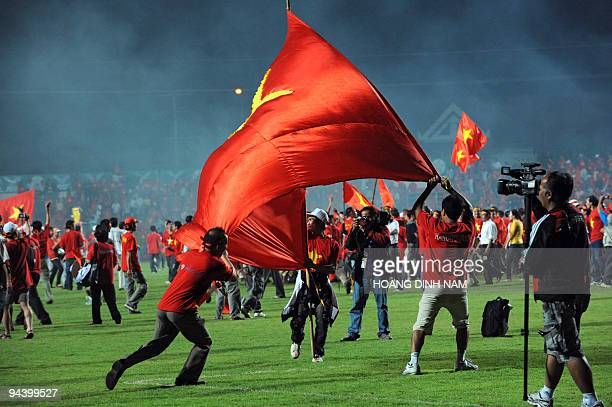 Thousands of Vietnamese fans wearing red Tshirts and holding Vietnamese flags take to the field after Vietnam defeated Singapore 41 in their...