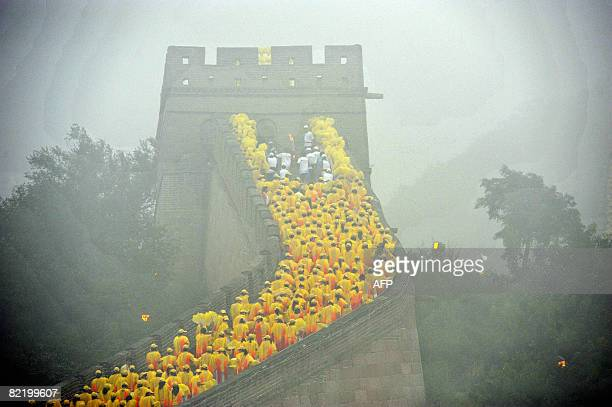 Thousands of volunteers line a section of the Great Wall in Badaling outside Beijing as a torchbearer carries the Olympic flame in the Olympic torch...