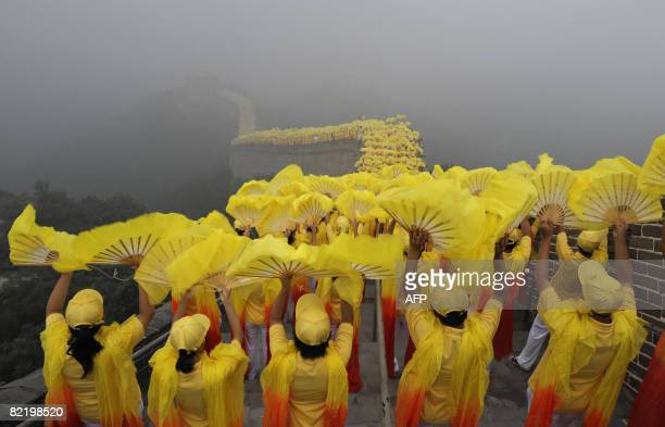 Thousands of volunteers perform during the Olympic torch ceremony as a section of the Great Wall in Badaling outside Beijing is shrouded in a haze on...