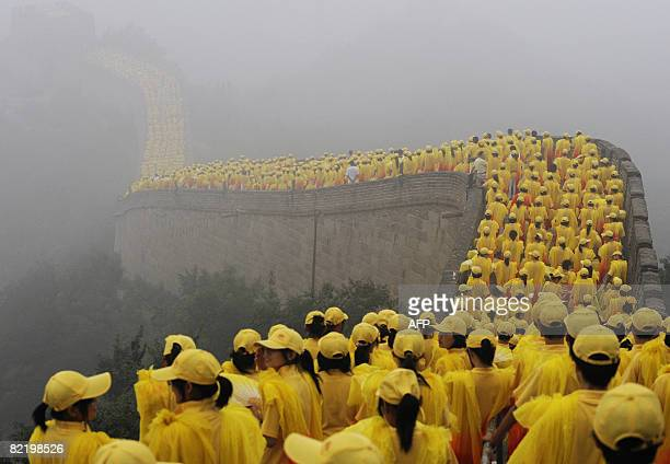 Thousands of volunteers take part in the Olympic torch ceremony as a section of the Great Wall in Badaling outside Beijing is shrouded in a haze on...