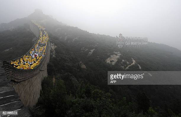 Thousands of volunteers wait along a section of the Great Wall in Badaling outside Beijing to take part in the Olympic torch ceremony and relay on...