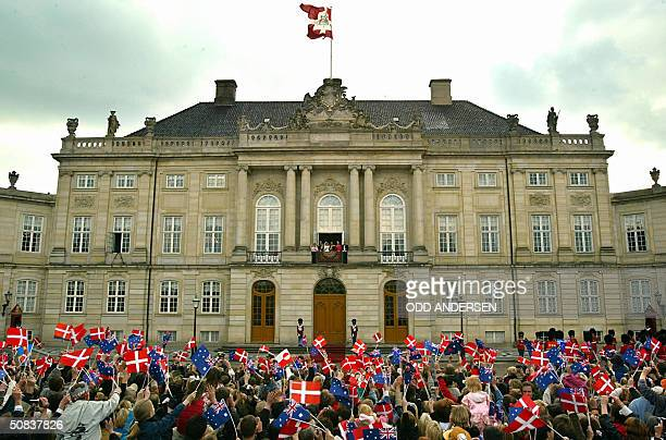 Thousands of wellwishers wave flags at Crown prince Frederik and Crown princess Mary of Denmark standing on the balcony at Amalienborg castle in...