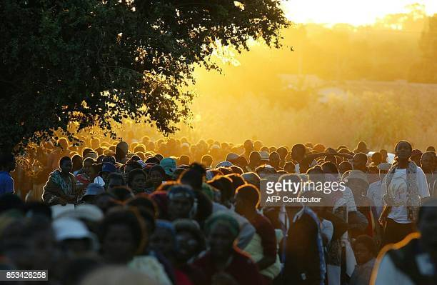 Thousands of Zimbabweans still stand in a queue wating to cast their vote 10 March 2002 at a Harare polling station Thousands still remained in...