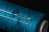 coil of dark blue thread and two needles macro