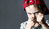 threatening 6-year old boy with freckles and a red hat back looking violent with fists in the forefront,acting like a little bully at school, contrast effects over grey background studio