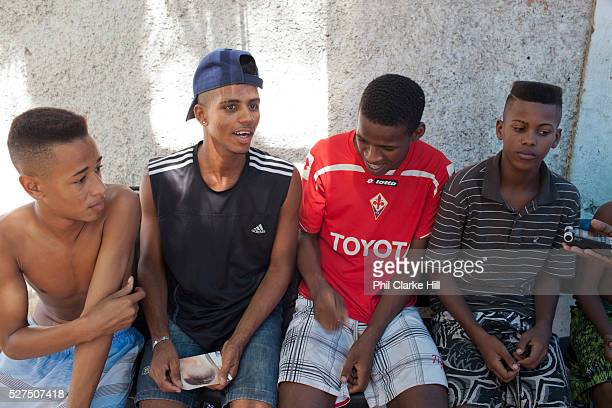 Three 3 young Brazilian men sitting on a bench in the street Young independent barber shop hair stylist in the street for the young people guys of...