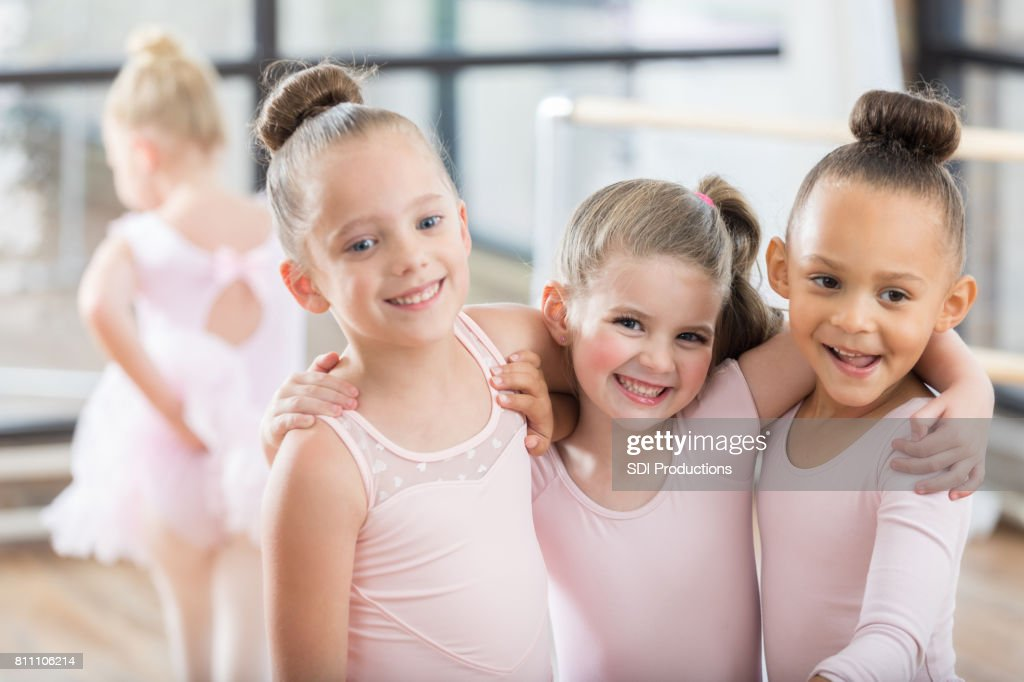Three adorable young ballerinas smile arm in arm : Stock Photo