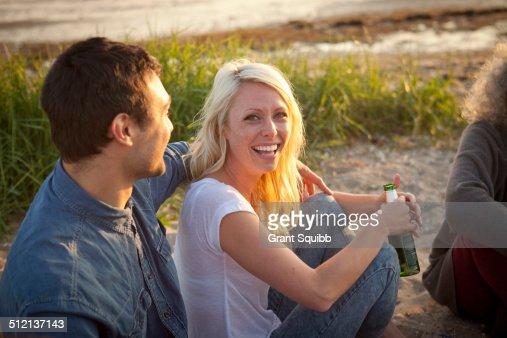 Three adult friends drinking beer on Bournemouth beach, Dorset, UK