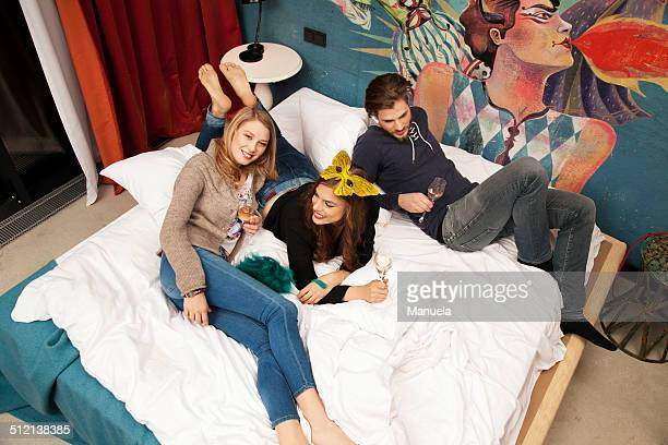 Three adult friends lying on hotel bed drinking champagne