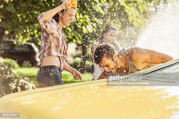 Three adult friends washing car and fooling around